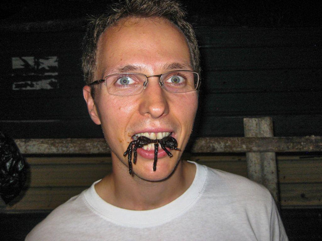 Greasy as heck from the humidity, eating fried tarantula in Cambodia.